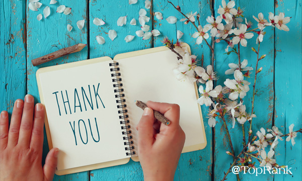 Hands creating thank you in a book surrounded simply by flowers image.